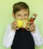 Ragazzo in contenitore di pranzo e di uniforme scolastico con il panino ed i frutti Fotografie Stock Libere da Diritti