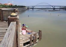 Ragazzo coraggioso che si siede accanto al ponte oltre dieci metri a partire dal mare Fotografia Stock