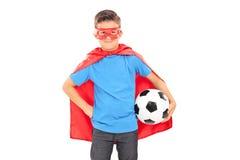 Ragazzo in costume del supereroe che tiene un calcio Immagine Stock