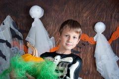 Ragazzo in costume di Halloween con la zucca arancio Fotografia Stock