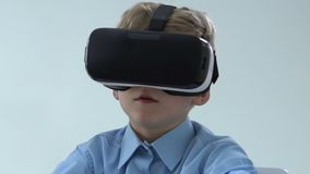 Ragazzo in cuffia avricolare di realtà virtuale, tecnologia dell'innovazione, dispositivo di spettacolo stock footage