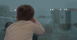 Ragazzo curioso che esamina aereo mentre aspettando il volo stock footage