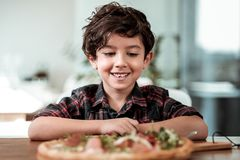 Ragazzo dagli occhi scuri che si siede alla tavola con pizza con bacon e formaggio fotografia stock