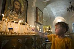 Ragazzo dalle candele nel tempio immagine stock