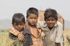 Ragazzo dei giovani di Portret tre nel cammello Mela, India di Pushkar fotografia stock libera da diritti