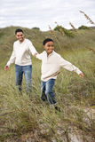 Ragazzo del African-American che tira padre sulle dune di sabbia fotografie stock libere da diritti