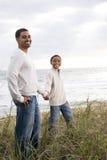Ragazzo del African-American con il padre sulle dune di sabbia fotografia stock libera da diritti