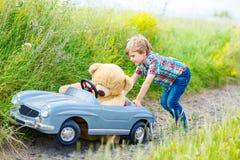 Ragazzo del bambino che conduce la grande automobile del giocattolo con un orso, all'aperto fotografie stock