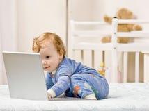 Ragazzo del bambino che digita sul computer portatile in camera da letto Immagini Stock