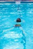 Ragazzo del bambino che fa la concorrenza di nuoto in stagno fotografie stock