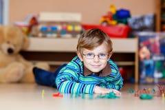 Ragazzo del bambino che gioca con i soldatini all'interno a Fotografia Stock Libera da Diritti