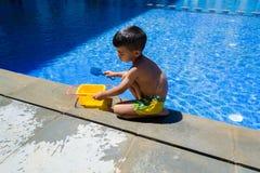 Ragazzo del bambino che gioca con i suoi giocattoli sull'orlo di una piscina Fotografia Stock