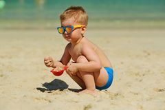 Ragazzo del bambino che gioca con la pala e la sabbia sulla spiaggia Immagine Stock