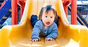 Ragazzo del bambino che gioca sul campo da giuoco fotografia stock