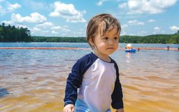 Ragazzo del bambino che gioca in un lago un giorno di estate immagini stock