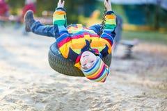 Ragazzo del bambino che oscilla sul campo da giuoco all'aperto Immagini Stock Libere da Diritti