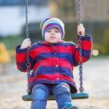 Ragazzo del bambino che oscilla sul campo da giuoco all'aperto Fotografie Stock Libere da Diritti