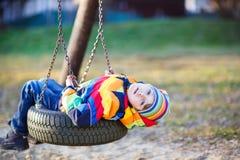 Ragazzo del bambino che oscilla sul campo da giuoco all'aperto Immagine Stock Libera da Diritti