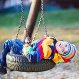 Ragazzo del bambino che oscilla sul campo da giuoco all'aperto Fotografia Stock