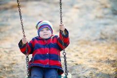 Ragazzo del bambino che oscilla sul campo da giuoco all'aperto Immagine Stock