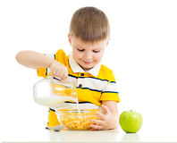 Ragazzo del bambino con i fiocchi di mais e latte isolato Fotografie Stock