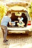 Ragazzo del bambino che si siede nel tronco di automobile appena prima andare per il viaggio Fotografia Stock