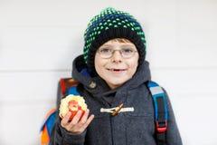 Ragazzo del bambino con i vetri dell'occhio che cammina dalla scuola e che mangia mela Fotografia Stock Libera da Diritti
