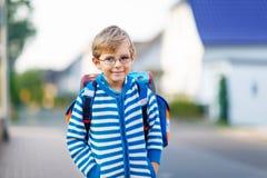 Ragazzo del bambino con la cartella della scuola sul modo alla scuola Immagine Stock