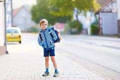 Ragazzo del bambino con la cartella della scuola sul modo alla scuola Immagini Stock