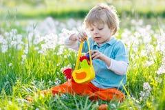 Ragazzo del bambino divertendosi con la caccia tradizionale dell'uovo di Pasqua Fotografie Stock