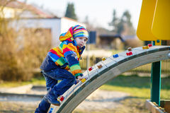 Ragazzo del bambino divertendosi sul campo da giuoco all'aperto Fotografia Stock Libera da Diritti