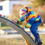 Ragazzo del bambino divertendosi sul campo da giuoco all'aperto Immagini Stock Libere da Diritti