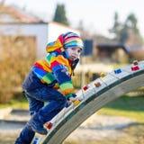 Ragazzo del bambino divertendosi sul campo da giuoco all'aperto Immagine Stock Libera da Diritti