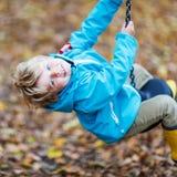 Ragazzo del bambino divertendosi sul campo da giuoco di autunno Immagini Stock