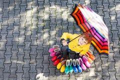 Ragazzo del bambino e gruppo di stivali di pioggia variopinti Bambino biondo che sta sotto l'ombrello fotografia stock libera da diritti