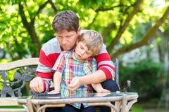 Ragazzo del bambino ed il suo giovane padre che giocano insieme il gioco dei controllori bambino ed uomo che spendono insieme sva fotografie stock libere da diritti