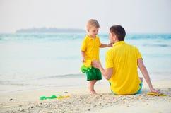 Ragazzo del bambino sulla spiaggia con il padre immagini stock