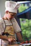 Ragazzo del cuoco unico che taglia le fragole a pezzi Immagine Stock