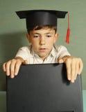 Ragazzo del Preteen in computer portatile di apertura del cappello di graduazione Immagine Stock Libera da Diritti