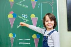 Ragazzo del primo grado alla scuola, mostrante i numeri e calcolazione Fotografia Stock