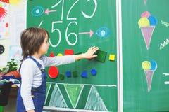 Ragazzo del primo grado alla scuola, mostrante i numeri e calcolazione Immagini Stock Libere da Diritti