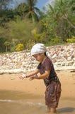 Ragazzo del ritratto che gioca con la sabbia dal mare fotografia stock libera da diritti