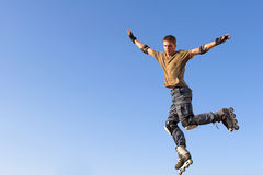 Ragazzo del rullo che salta dal parapetto sul cielo blu fotografia stock libera da diritti
