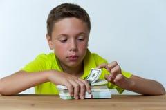 Ragazzo del Tween che si siede alla tavola con le banconote in dollari Immagine Stock Libera da Diritti