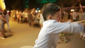 Ragazzo dell'adolescente che sorride alla macchina fotografica Notte sulla via balli, giochi lo sciocco stock footage