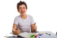 Ragazzo dell'adolescente su compito che sorride e che mostra pollice Immagine Stock