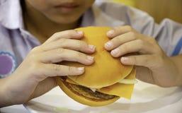 Ragazzo dell'Asia del pesce e del formaggio dell'hamburger a disposizione che tiene il cibo fotografie stock
