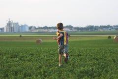 Ragazzo dell'azienda agricola che funziona attraverso il campo Immagini Stock