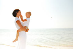 Ragazzo della holding della donna sulla spiaggia fotografie stock libere da diritti