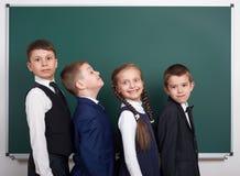 Ragazzo della scuola elementare vicino al fondo in bianco della lavagna, vestito in vestito nero classico, allievo del gruppo, co Fotografia Stock Libera da Diritti